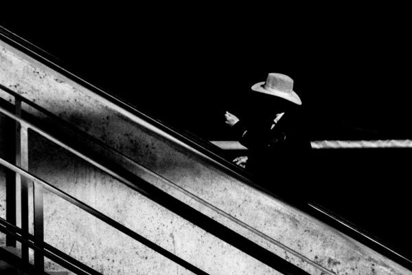 Man with hat on escalator